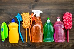 Housekeeping tool. Detergents, soap, cleaners and brush for housecleaner work on wooden background top view space for stock photos