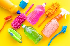 Housekeeping tool. Detergents, soap, cleaners and brush for housecleaner work on yellow background top view space for royalty free stock photography