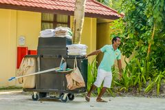 Housekeeping worker dragging the cart with cleaning tools royalty free stock image