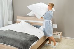 Housekeeping worker with pillows Stock Photos
