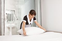 Housemaid beating pillows in hotel room. Portrait of nice neat lady who works as maid making bed while owners of house. Are absent, cleaning and removing dirt Stock Image