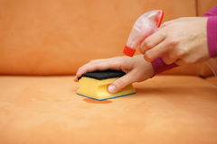 Housemaid is cleaning stain on sofa with spray bottle and sponge Stock Image