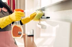 Housemaid cleans furniture with a cleaning spray. Housemaid hands in gloves cleans furniture with a cleaning spray, hotel room interior on background stock photos