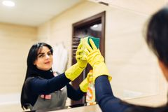Housemaid cleans the mirror with a cleaning spray. Housemaid hands in rubber gloves cleans the mirror with a cleaning spray, hotel bathroom interior on stock images