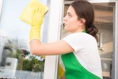 Housemaid with cloth washing window Stock Image