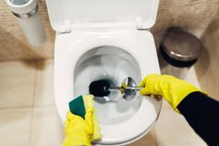 Housemaid in gloves cleans the toilet with brush. Housemaid hands in rubber gloves cleans the toilet with brush, hotel restroom interior on background stock photo