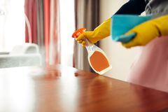 Housemaid hands cleans table with cleaning spray. Housemaid hands in gloves cleans the table with a cleaning spray, hotel room interior on background stock image