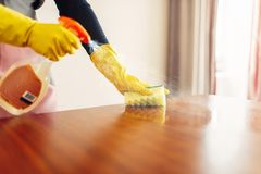 Housemaid hands cleans table with cleaning spray. Housemaid hands in gloves cleans the table with a cleaning spray, hotel room interior on background royalty free stock photos