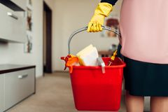 Housemaid hands in gloves holds cleaning equipment. Corridor of hotel on background. Professional housekeeping, charwoman stock photography