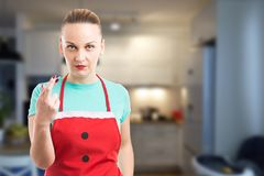 Housemaid or housekeeper making bad luck gesture with fingers cr Royalty Free Stock Image
