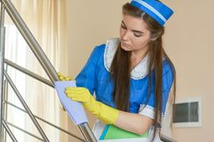 Housemaid with rag working. Stock Photo