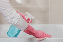 Housemaid in the rubber gloves cleaning bathroom with a sponge. Housemaid cleaning a bathroom, closeup shot stock photos