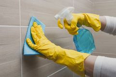 Housemaid in the rubber gloves cleaning bathroom with a sponge. Housemaid cleaning a bathroom, closeup shot royalty free stock photos