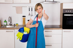 Housemaid Showing Thumbs Up In Kitchen Royalty Free Stock Images