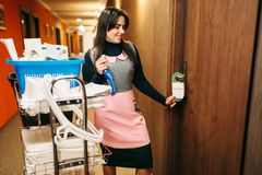 Housemaid in uniform finished cleaning the room. Corridor of hotel on background. Professional housekeeping, charwoman royalty free stock images