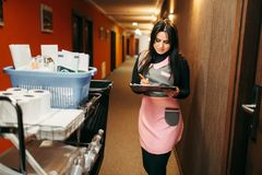 Housemaid in uniform makes notes in notepad. Cart with detergents, hotel corridor interior on background. Cleaning service, professional housekeeping royalty free stock images