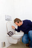 Houseman. Housman cleaning a toilette with lavatory brush Stock Photo