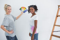 Housemates picking colour for blank wall and smiling at camera Stock Photography