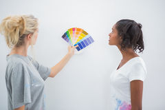 Housemates picking colour for blank wall Royalty Free Stock Images