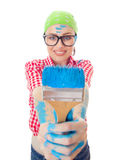 Housepainter. Happy woman with a paint brush holding it out at arms while painting a wall, face in a focus, isolated on white Stock Images