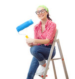 Housepainter. Smiling woman sitting on ladder and holding roller, isolated on white Stock Photography