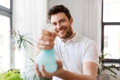 Houseplants de pulverização do homem com água em casa fotos de stock royalty free