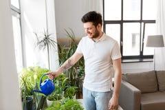 Houseplants molhando do homem em casa fotos de stock