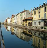 Houses along the Naviglio Grande in Milan on a bright summer morning, reflected in the calm water of the canal royalty free stock photography