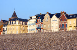 Houses along pebble beach. Pebble beach at the Treport in the Somme bay in France Stock Photos