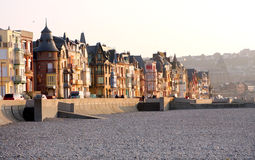 Houses along pebble beach. Pebble beach at the Treport in the Somme bay in France Royalty Free Stock Image