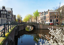 Houses of Amsterdam, Netherlands. Houses and bridge over canal with mirror reflections at blooming spring, Amsterdam, Netherlands Stock Photo