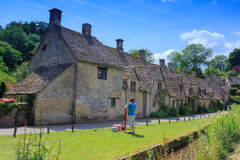 Houses of Arlington Row in Bibury Village, England. BIBURY, ENGLAND, UK - JULY 9, 2014: Unidentified man are keeping his picnic tool at the Cotswold stone Stock Photo