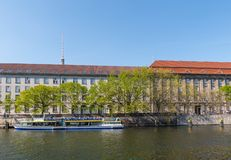 Houses on the banks of river Spree with trees and a canal tour boat. Berlin Germany - April 20. 2018: Houses on the banks of river Spree with trees and a canal stock photography