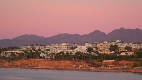 Houses on the beach. In the background, the mountains and the sky are illuminated by the morning sun. Egypt Sharm El Sheikh stock footage