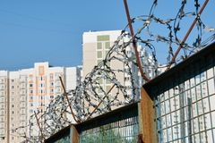Houses behind a barbed wire fence stock photos