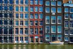 houses and boat on Amsterdam canal Damrak with reflection. Ams royalty free stock photography