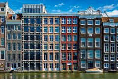 houses and boat on Amsterdam canal Damrak with reflection. Ams royalty free stock photo