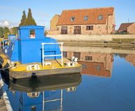 Houses and boat next to a river with reflection Royalty Free Stock Photography