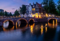 Amsterdam Canals at Night. Houses and boats along the intersection go the Keizersgracht and Leidsegract canals in Amsterdam during the evening. The canals are a stock photo