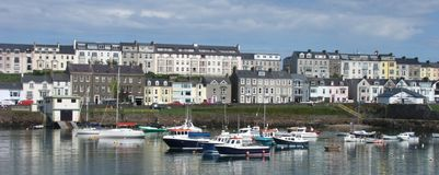 Houses and boats in the harbour by the irish sea Co. Antrim Northern Ireland 2017 with  blue sky background for editors text copy. Houses and boats in the stock photography