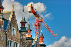 Crane over buildings in Bruges, Belgium Royalty Free Stock Photos