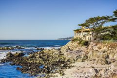 Houses build on the cliffs on the Pacific Ocean, Carmel-by-the-Sea, Monterey Peninsula, California. Blue sky background royalty free stock image