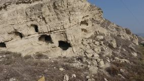 Houses built into the hill next to the ancient city. In the Turkey stock video