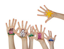 Houses, car and trees painted on children hands. Hands raised up Royalty Free Stock Images
