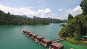 Houses at Cheow Lan Lake, Khao Sok National Park in southern Thailand. HD Aerial Slowmotion. Houses at Cheow Lan Lake, Khao Sok National Park in southern stock video footage