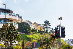 Houses on a cliff hill, on a rock among green plants, an interes Stock Photos