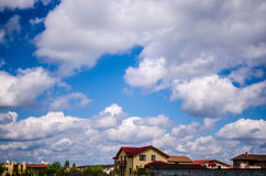 Houses, clouds on blue sky Stock Photos