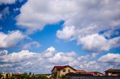 Houses, clouds on blue sky Stock Photos