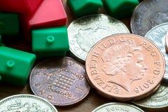 Houses di modello di plastica e monete inglesi Fotografia Stock Libera da Diritti