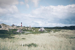 Houses in dunes near Hörnum on the Island of Sylt, Germany with typical red and white lighthouse Royalty Free Stock Images